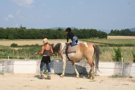 une monitrice apprend à une enfant la voltige à cheval pendant une colo été
