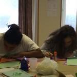 les filles sont concentrées pendant une activité manuelle en séjour de vacances adaptées
