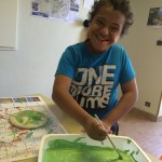 un enfant fait de la peinture en séjour de vacances adaptées