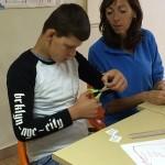 un enfant et une animatrice pendant une activité manuelle en séjour de vacances adaptées