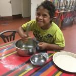 un enfant prépare la pate à cookies en séjour de vacances adaptées